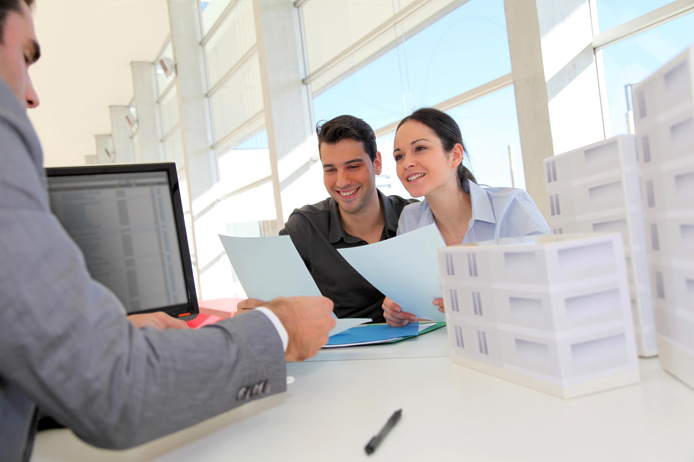 Couple discutant avec un agent immobilier